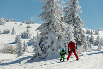 Father and son skiing together