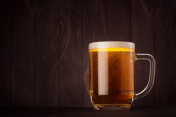 Mug beer glass with golden sparkling lager on dark wood board, copy space. Template for advertising, design, branding identity, restaurant menu, cover.