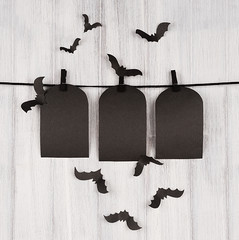 Halloween advertising mock up. Blank black sale labels tomb hanging on clothespins, flock bats and white wooden plank background. Template for design, cover.