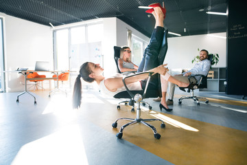 Wall Mural - Business woman riding a chair and racing in the workplace.