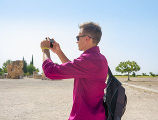 Young man with backpack, tourist, takes pictures with his mobile phone view of the ruins of the city of Hierapolis, modern name of the location - Pamukkale, Turkey.