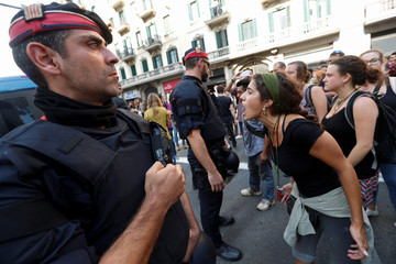 A woman shouts slogans against Spanish National Police during a gathering outside National Police police station, in Barcelona