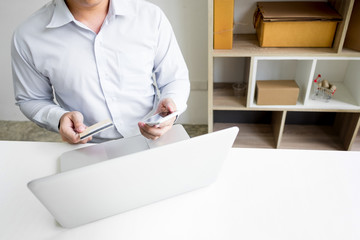 Man holding credit card in hand and entering security code using smart phone on laptop keyboard, online shopping concept