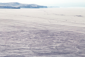 Car trails on the frozen lake surface covered with snow/ Lake Baikal