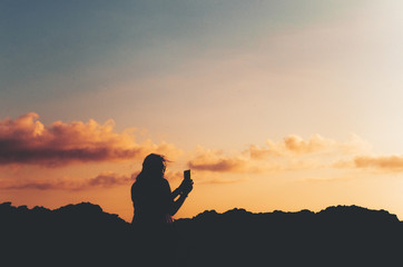 Anonymous, unrecognizable silhouetted female taking a photo of a beautiful sunset with smartphone