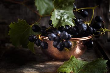 Purple grapes in copper bowl