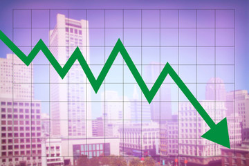 Real estate market economy with decreasing graph and green arrow going down with colorful blurred cityscape background