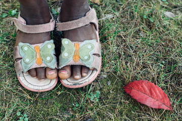 Fallen red leaf next to a black girl's feet wearing sandals