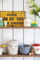 Shelves in a kitchen with fun retro items, bowls and canisters