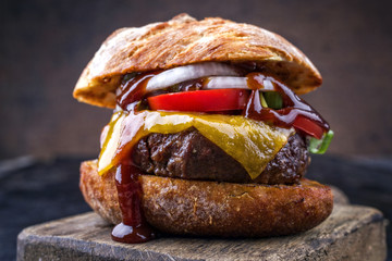 Barbecue wagyu cheeseburger with onions and tomatoes as close-up on a cutting board