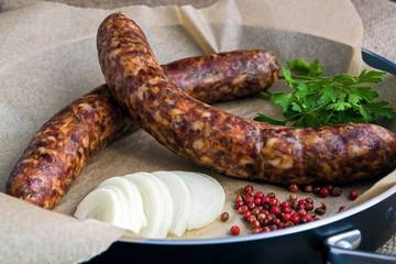 Two raw sausages in a frying pan with onion, spices and parsley