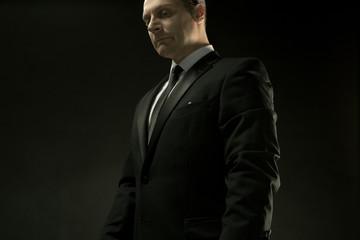 The attractive man in black suit on dark background