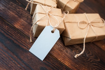 Mockup boxes for gifts of kraft paper and gift tags on a wooden background