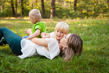 Family concept, mother playing with her kids and kissing her daughter on the grass