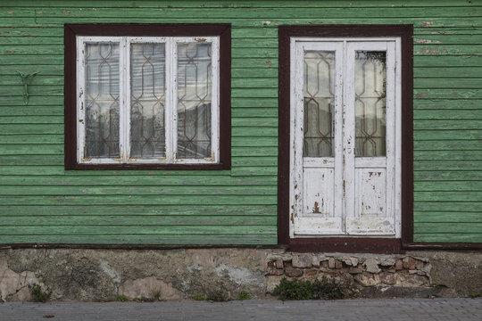 Door and window in green wooden house