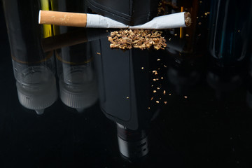 Tobacco cigarette crushed under electronic cigarette surrounded with e-juice bottles