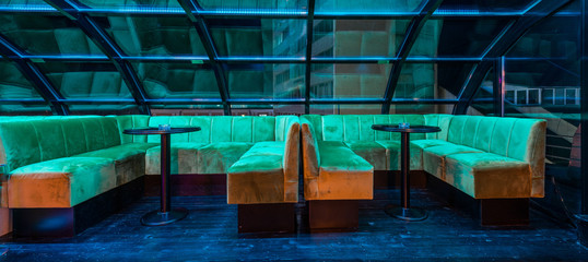 Modern sofas under skylight by night in lounge bar interior