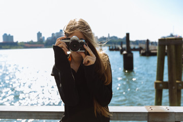 Attractive woman holding a vintage camera outdoors