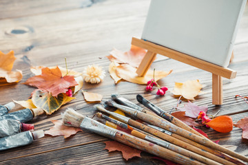 Canvas on easel, paint tubes, brushes for painting and autumn leaves on old wooden background. Retro toned.