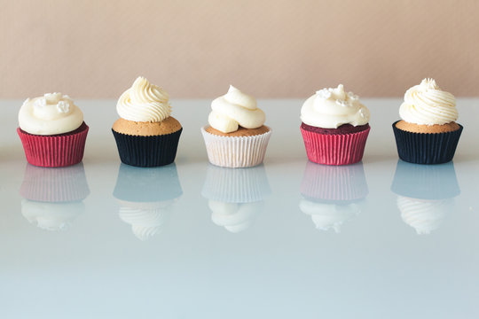 A row of six cupcakes on a glass table with reflection