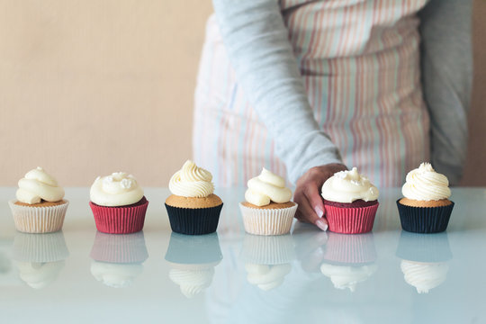 Hand of a woman in an apron picking out a cupcake