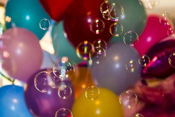 Soap bubbles against the background of inflatable balls