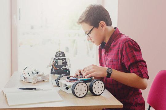Stem education. Boy creating robot at lab