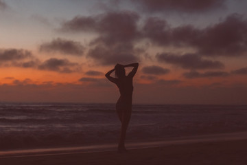 Silhouette of a young woman on the beach at sunset