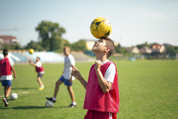 Boy Balancing a Football on His Head