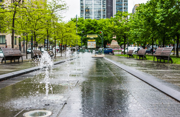 Victoria Square Metro station park with fountains during rainy cloudy day in city in Quebec region