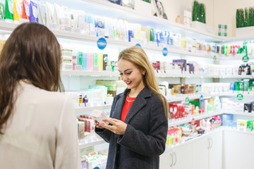 Young business woman in perfumery shop choose cosmetics with consultant