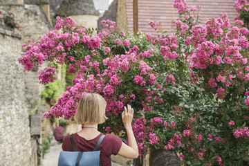 Young blond woman touching pink flowers on a bush