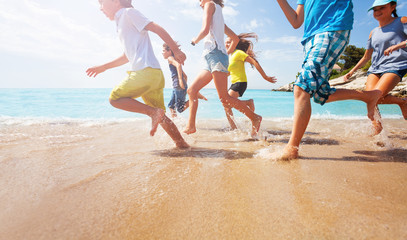 Close-up of running kids legs in shallow sea water