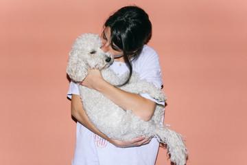 Brunette woman hugging and kissing her dog