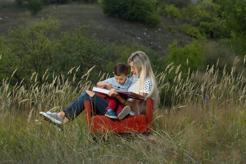 mother and son on nature sitting on the couch reading a book