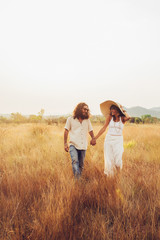Good-Looking Young Couple Walking and Laughing Together in Dry Grassland