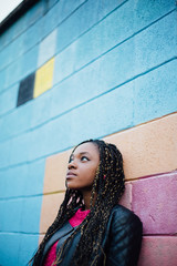 African girl leaning against a colorful wall