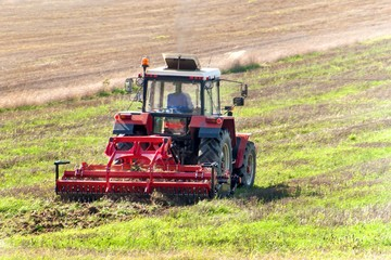 Red tractor in the field. Agricultural farm work. Agriculture in the Czech Republic.