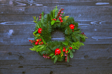 Decorative christmas wreath on the snow winter door, soft focus, top view