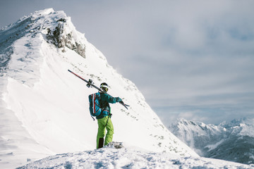 male skier standing alone on top of a snowcovered summit looking to the surrounding peaks