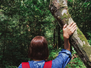 Hipster young girl with backpack walking in forest. Camping ,Adventure ,Travel and vacation Concept.