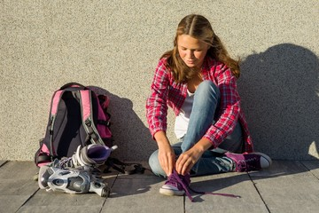 Girl teen removes sneakers and clothes roller skates outdoor.
