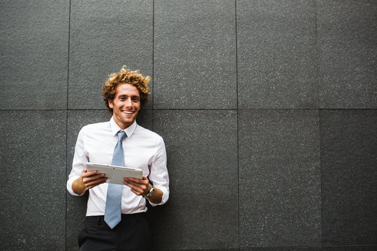 Smiling young man using his digital tablet
