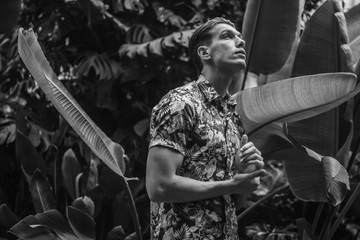 black and white portrait of fashionable man in floral shirt in nature