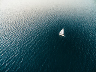 Aerial drone image of a sailboat sailing into sunset