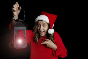 Merry Christmas. A young girl in a red sweater and a Santa Claus hat holds a black lantern.
