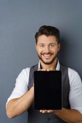 lächelnder geschäftsmann zeigt den bildschirm seines tablets