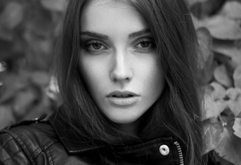 Fashionable black and white photo from a magazine. beautiful young rocker in a heavy leather jacket, with long beautiful black hair posing on the background grid and Park