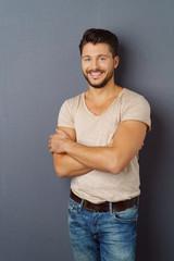 lächelnder mann steht vor grauer wand im studio