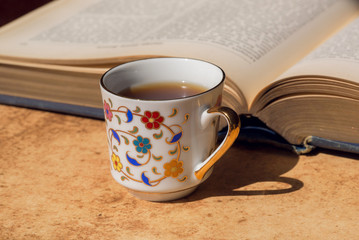 Breakfast of smart man concept. Old book and floral design cup of coffee. Selective focus